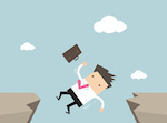 Businessman falling from gap of cliff.